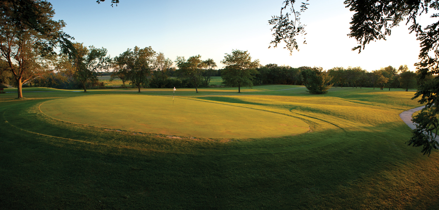 View of a hole on the course at sunset at Coachman's Golf Resort